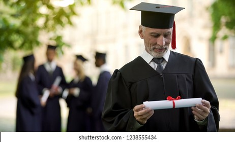 Senior man in academic regalia holding diploma, education at any age, new degree