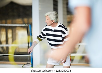 Senior man in activewear standing on badminton court while concentrating on game