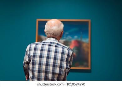 Senior man admiring artwork in museum. Rear view.