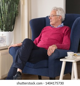 Senior man alone sitting in chair and looking outside