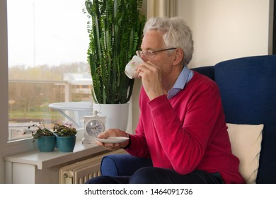 Senior man alone sitting in chair drinking coffee