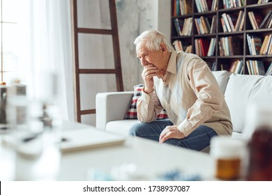 Senior man alone sitting on sofa at library table with medicines close-up crying emotional covering mouth