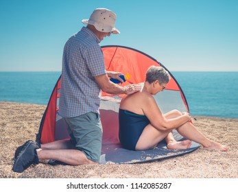 A senior man is applying sun cream to his wife's back