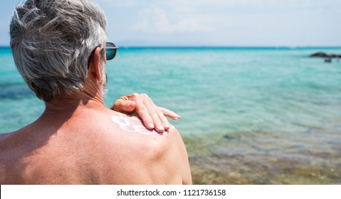 Senior man applying sun lotion on summer vacation back view