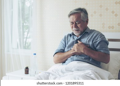 Senior man Asian suffering from bad pain in his chest heart attack at home - senior heart disease