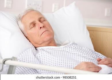 Senior man asleep in hospital bed