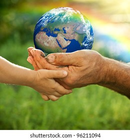 Senior man and baby holding the Earth in hands against a rainbow in spring. Elements of this image furnished by NASA