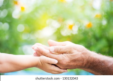 Senior man and baby holding empty hands against green spring background