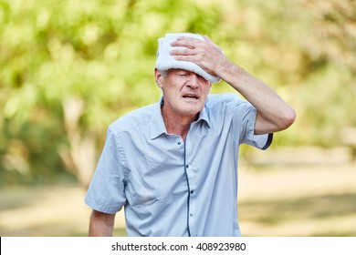 Senior man with bad circulation cools his head with wet cloth