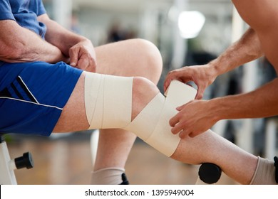 Senior man with bandage on leg after injury in gym. Male hands fixed elastic bandage on male injured leg. Sport and health.