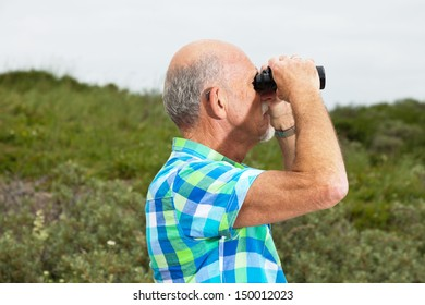 Senior man with beard and glasses using binoculars outdoors in grass dune landscape. Wearing green blocked shirt.