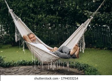 Senior man with a beard lying in a hammock in the garden. Man relaxes in a garden hammock