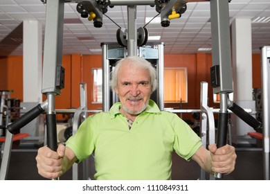 Senior man with a beard and mustache in the gym, working out with weights