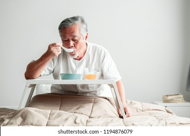 Senior man in bed enjoying breakfast. Old asian male with white beard eating congee and orange juice. Senior home service concept.