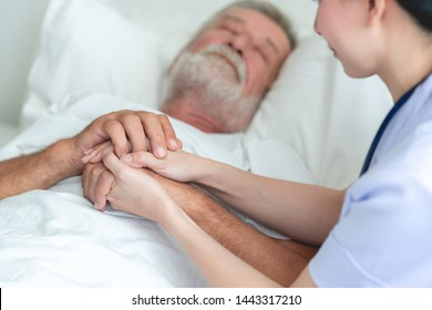 Senior man in bed with nurse in retirement home. Caucasian male with asian woman. Holding hands while he sleeps.
