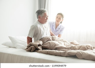 Senior man in bed trying to get up and nurse helping him. Old asian man and beautiful asian nurse woman in bedroom and open curtain. Senior home service concept.