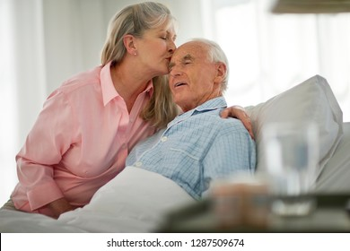 Senior man being kissed on the forehead by his wife as he lies in bed.