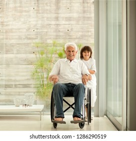 Senior man being pushed in wheelchair by his grandson.