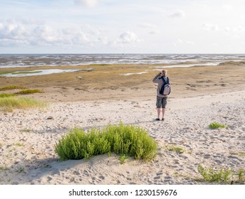 Senior man with binoculars looking at dried out boat on tidal flats at low tide of Wadden Sea from beach of Boschplaat on Terschelling, Netherlands