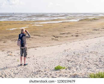 Senior man with binoculars looking at tidal flats at low tide of Wadden Sea from beach of Boschplaat on Terschelling, Netherlands