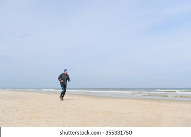 Senior man in black clothes running at the beach