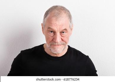 Senior man in black t-shirt, looking serious, studio shot.
