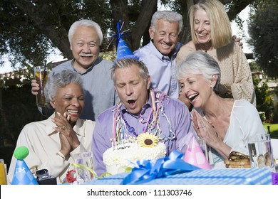 Senior man blowing candles with family and friends