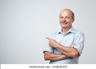 Senior man in blue shirt pointing with index finger to important information on copyspace isolated on a white background