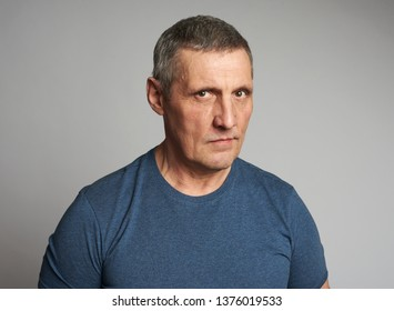 Senior man in blue t-shirt isolated on grey background