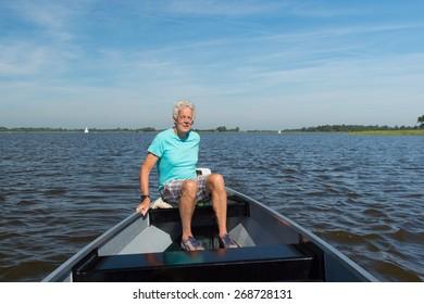 Senior man in boat in Dutch landscape province Overijssel