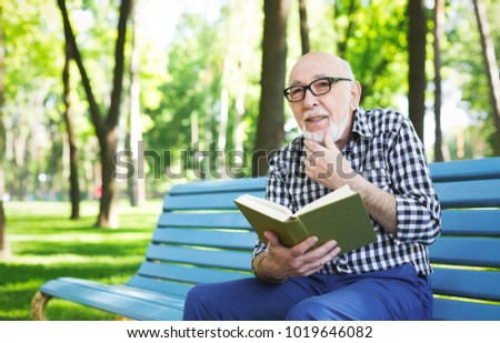 82ee62d038d60 Senior man with a book outdoors. Elderly casual man in eyeglasses having  rest