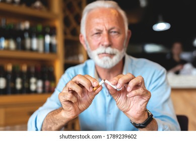 Senior man breaking cigarette as it is injurious to health
