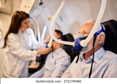 Senior man breathing through mask during oxygen therapy in hyperbaric chamber.