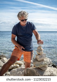 Senior man building stone pile on the beach in Rovinj. Croatia, June 2018.
