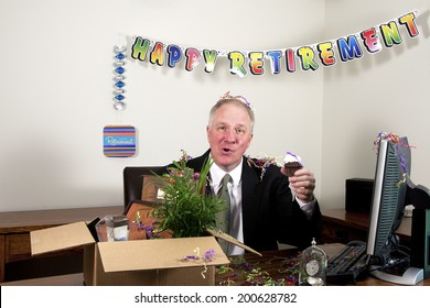 Senior man in a business suit sitting behind a desk with retirement banner, box full of personal effects holding a cupcake