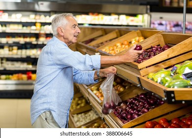 Senior man buying red onion at the grocery shop