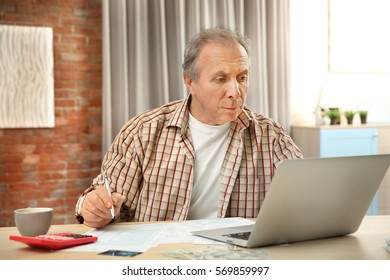 Senior man calculating taxes at home