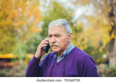 Senior man calling on smartphone in park.Technology, people, lifestyle and communication concept.