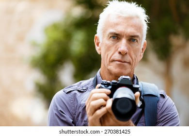 Senior man with camera in city
