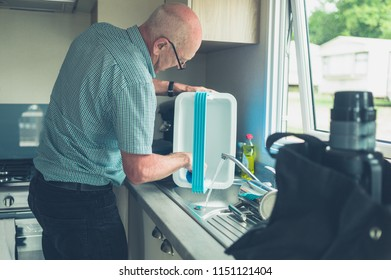 A senior man in a caravan is cleaning is cooler box