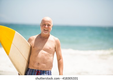 Senior man carrying surfboard on a sunny day