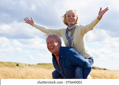Senior Man Carrying Senior Woman On Walk In Countryside