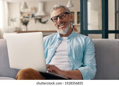 Homme de haut niveau vêtu de vêtements décontractés utilisant son ordinateur portable et regardant la caméra avec le sourire tout en étant assis sur le canapé à la maison