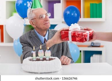 Senior man celebrating 100th birthday and receiving gift