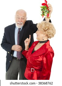 Senior man chasing a beautiful woman around trying to get her under the Christmas mistletoe.  Isolated on white.