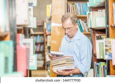 Senior man chooses books in the library