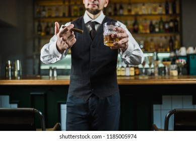 senior man with cigar and whiskey on the bar counter. No face