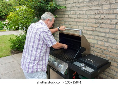 Senior man cleaning barbecue in his back garden