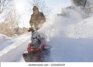 Senior man clearing snow from sidewalk with snowblower on windy day.