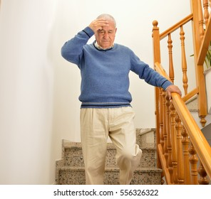 senior man coming down the stairs and having a dizziness at home by the influenza or flu
